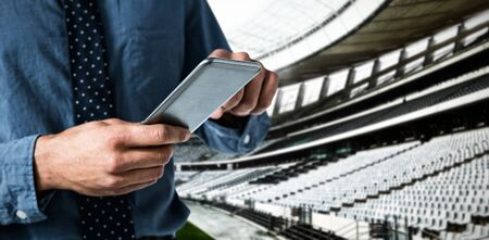 Mid-section of business man using smartphone against rugby stadium at dawn