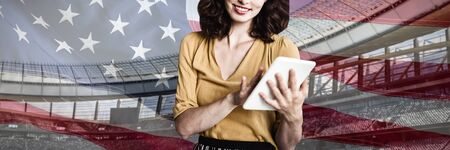 Portrait of woman using digital tablet against close-up of an american flag