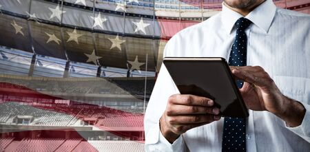 Upper mid-section of man using a tablet against close-up of an american flag