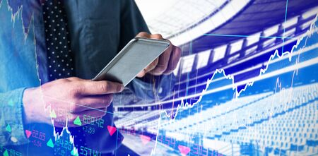 Mid-section of business man using smartphone against stocks and shares