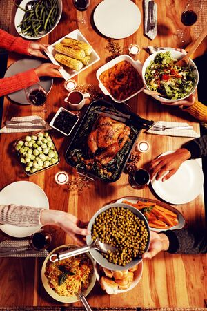 Overhead view of a group of young adult multi-ethnic male and female friends sitting around a table holding dishes and serving Thanksgiving dinner at home together