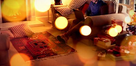 Composite image of brown parquet against man at home at christmas time