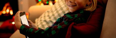 Portrait of a young Caucasian boy using a tablet in the sitting room at Christmas time, smiling to camera