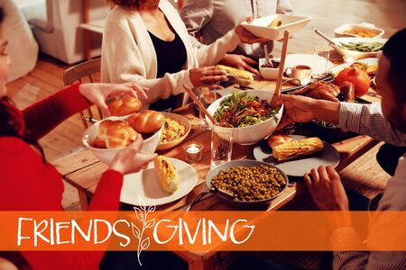 Happy Friendsgiving against millennial adult friends celebrating thanksgiving together at home Archivio Fotografico