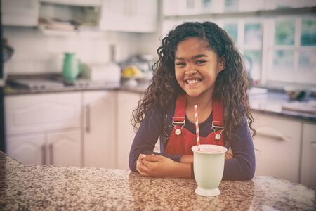 Portrait of a young mixed race girl sitting in a kitchen at Christmas, smiling to camera with a mug and a straw in front of her