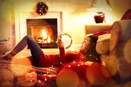 Composite image of brown parquet against woman at home at christmas time Stock fotó