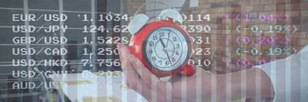 Cropped hand holding alarm clock against blue data Stock fotó