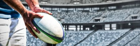 Rugby player against rugby ball on a stand in stadium
