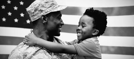 Side view close up of a young adult African American male soldier carrying his young son, both looking at each other and smiling, in front of a US flag