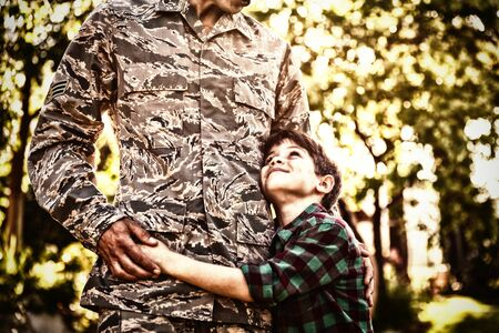 Front view mid section of a young adult mixed race male soldier in the garden outside his home, embracing his young son, who is looking up at him smiling, backlit by sunlight