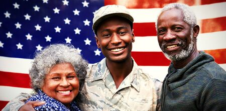 Portrait of a young adult African American male soldier embracing with his parents, all of them smiling to camera in front of a US flag Banque d'images