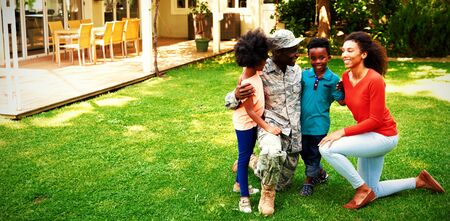 Front view of a young adult African American male soldier in the garden outside his home, kneeling with his arms around his young son and daughter, his mixed race wife beside them, all smiling at each other
