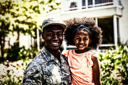 Portrait close up of a young adult African American male soldier in the garden outside his home, holding his young daughter, both smiling to camera Banque d'images
