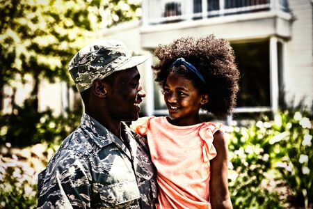 Front view close up of a young adult African American male soldier in the garden outside his home, holding his young daughter, both looking at each other smiling