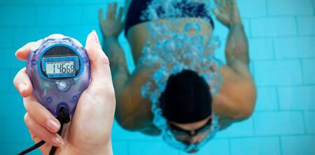 Close up of a hand holding a timer on a white background against swimmer in the water