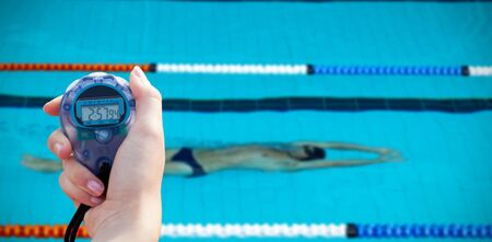 Close-up of a woman holding a chronometer to measure performance against swimmer in the water