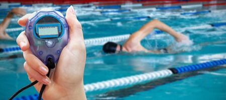 Close up of woman is holding a stopwatch on a white background against swimmers swimming in the pool