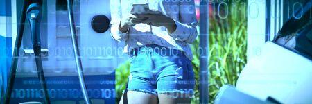 Interfaz contra la mujer que usa el teléfono móvil mientras se carga un coche eléctrico Foto de archivo