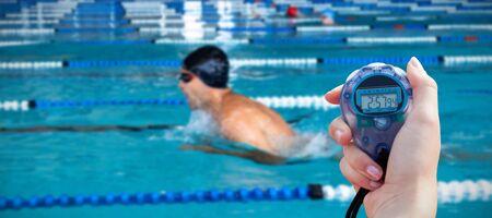 Primer plano de una mujer sosteniendo un cronómetro para medir el rendimiento contra el nadador nadando en la piscina