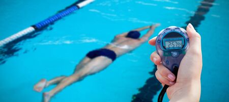 Close-up of a woman holding a chronometer to measure performance against swimmers swimming in the pool
