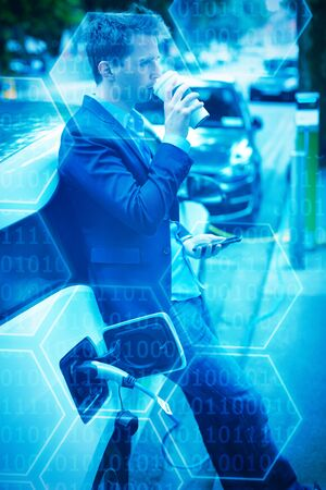 Black background with shiny hexagons against businessman having coffee while charging electric car