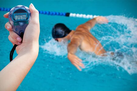 Close-up of a woman holding a chronometer to measure performance against swimmer swimming in the pool