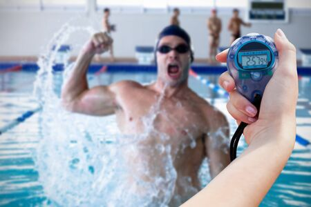Close-up of a woman holding a chronometer to measure performance against swimmer happy in the pool
