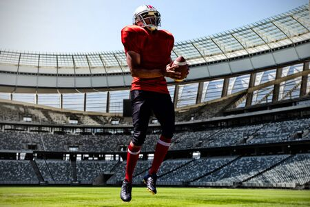 American Football Player against rugby goal post on a sunny day in the stadium 스톡 콘텐츠