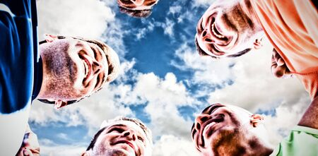 Sportsmen with arms around each other against blue sky with white clouds