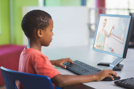 African american schoolboy using computer on video call with female teacher. Online education staying at home in self isolation during quarantine lockdown.
