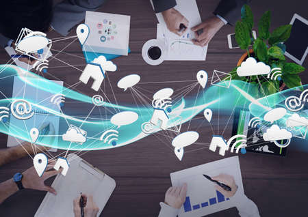 Network of digital icons against mid section of businesspeople working together. global networking and business technology concept Imagens