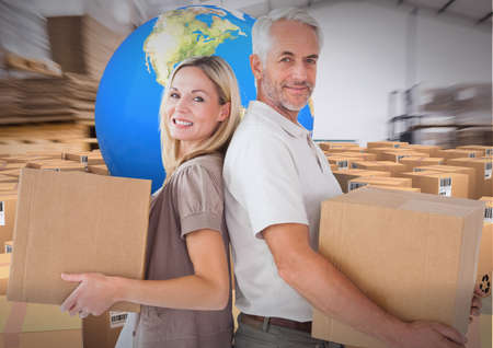 Composition of happy couple holding cardboard boxes with globe and boxes in warehouse. moving house, global shipment and delivery concept digitally generated image.