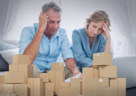 Composition of stack of cardboard boxes, worried man and woman reading bills. moving house, global shipment and delivery concept digitally generated image.