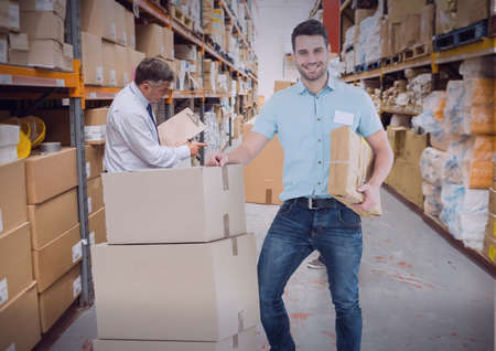 Composition of smiling delivery man with trolley of cardboard boxes in warehouse. moving house, global shipment and delivery concept digitally generated image. Archivio Fotografico