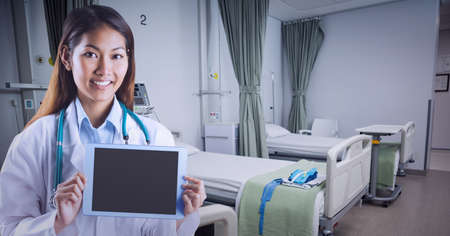 Portrait of caucasian female doctor holding digital tablet at hospital. healthcare and professionalism concept standing Standard-Bild