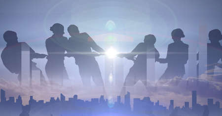 Composition of business people pulling rope over cityscape and glowing sun in background. global business and finance, connection and networking concept digitally generated image. Standard-Bild