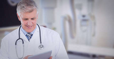 Portrait of caucasian senior male doctor using digital tablet at hospital. healthcare and professionalism concept