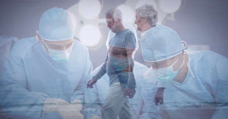 Team of surgeons performing operation at hospital against senior couple walking on the beach. healthcare and professionalism concept Standard-Bild