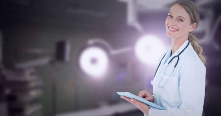 Portrait of caucasian female doctor wearing lab coat using digital tablet at hospital. healthcare and professionalism concept