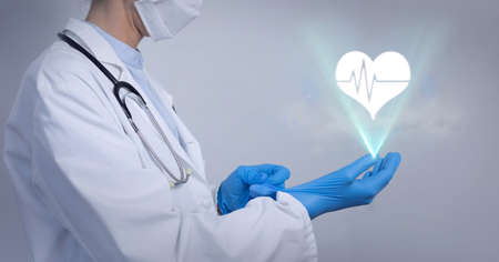 Human heart icon over mid section of male doctor wearing surgical gloves. medical research and technology concept Standard-Bild