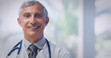Portrait of caucasian senior male doctor wearing lab coat smiling at hospital. healthcare and professionalism concept Standard-Bild