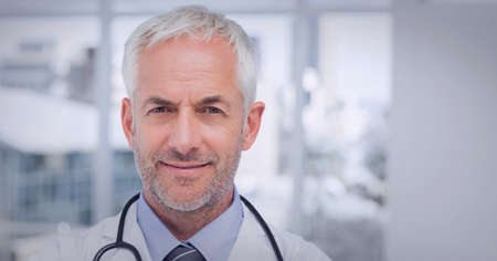 Potrait of male caucasian senior doctor wearing lab coat smiling at hospital. healthcare and professionalism concept Standard-Bild