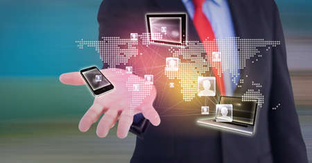 Composition of network of digital icons, world map and electronic devices over hand of businessman. global technology and digital interface concept digitally generated image. Standard-Bild