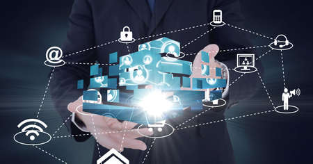 Composition of network of digital icons with glow over hands of businessman. global technology and digital interface concept digitally generated image. Standard-Bild