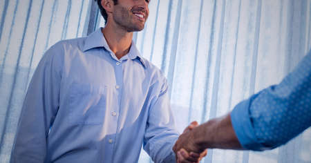 Businessmen smiling and shaking hands in office. global business, finances and networking concept digitally generated image. Standard-Bild