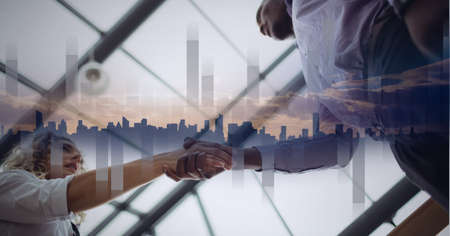 Composition of businessman and businesswoman shaking hands with statistics and cityscape. global finance, business and connection concept digitally generated image. Standard-Bild