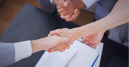 Businesswomen shaking hands over desk in office. global business, finances and networking concept digitally generated image.