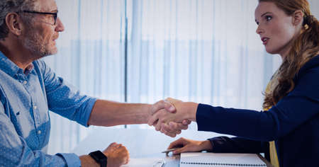 Businessman and businesswoman shaking hands over desk in office. global business, finances and networking concept digitally generated image.