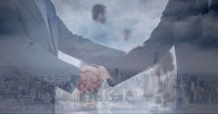 Composition of businessman and businesswoman shaking hands over cityscape. global business, finances and networking concept digitally generated image.
