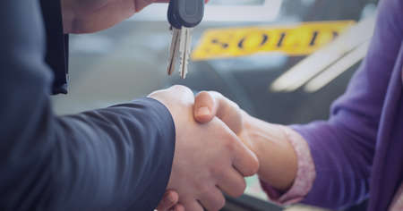 Man and woman shaking hands, man passing car keys. global business, finances and networking concept digitally generated image. Standard-Bild